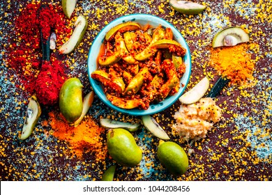 Close up of Aam ka achar or kari ka achar or traditional raw mango pickle with all its ingredients and speiceis on a wooden surface in drak Gothic colors.