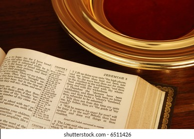 Close up of about half a page of a pulpit Bible next to a church collection plate. About half of the brass plate is visible.