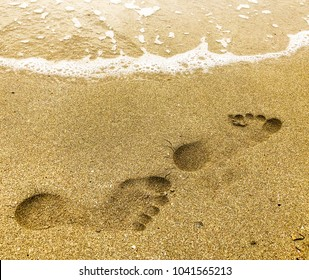 Close up abstract human footprints on sand beach. View of the sand and water on the beach