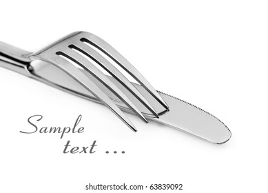 Close up abstract of a silver knife and fork on a white background with space for text