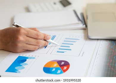 Close up of accountant working and analyzing financial reports project accounting with chart graph and calculator in modern office : finance and business concept.
