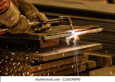 close up acetylene torch cutting metalwork with bright sparks