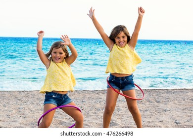 Close up action portrait of two little girls dancing with plastic rings on beach.