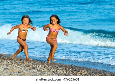 Close up action portrait of two young girls running together on pebble beach.