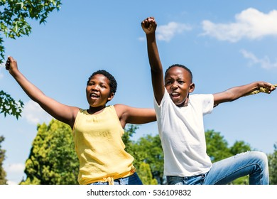 Close up action shot of african boy and girl raising hands and shouting in park.