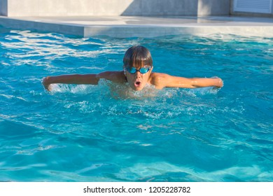 Close up action shot of boy swimming butterfly stroke. Sport, recreation, lifestyle concept