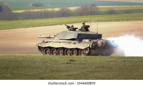 close up action shot of a British Army Challenger 2 FV4034 Main Battle Tank billowing a thick white smoke screen on a military exercise, Salisbury Plain, Wiltshire UK