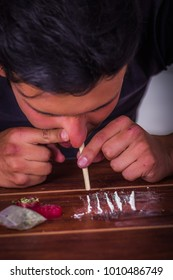 Close up of addicted man using a wrapped dollar bill inhaling cocaine, prepared over a wooden table
