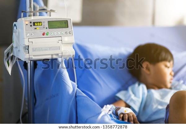 Close up adjust infusion pump set iv fluid intravenous drop saline drip with blurry patient boy in a hospital.