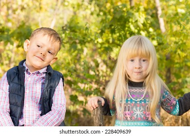 Close up Adorable White Little Toddlers in Autumn Fashion Outfit at the Park. Captured with Green Leafy Trees Background.