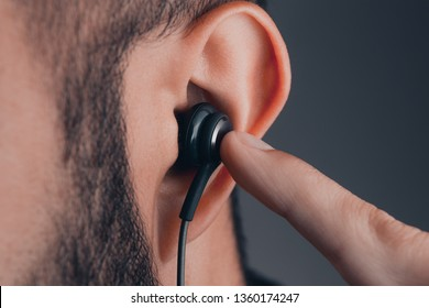 close up of adult caucasian male with earphones in the ear