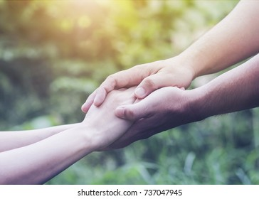 Close up adult man and woman holding hands together over blurred nature background. can be used for marriage and family or helping hands concept