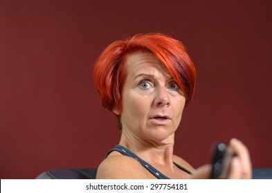 Close up Adult Redhead Woman Looking at the Camera with Shocked Facial Expression Against Dark Brown Wall.