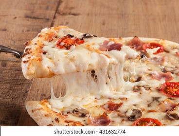 Close up af a hot pizza slice with dripping mozzarella cheese.