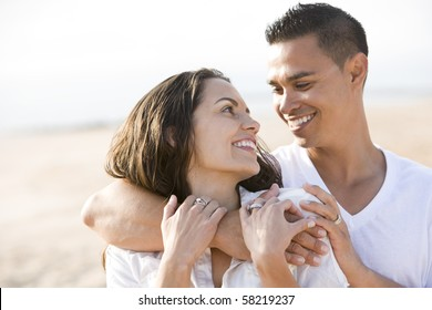 Close up of affectionate Hispanic couple on beach looking at each other