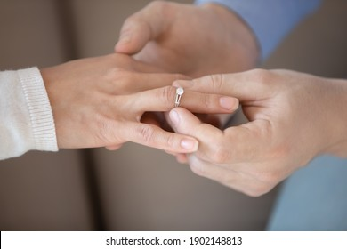 Close up affectionate man putting wedding ring on woman bride finger, loving boyfriend proposing marriage to girlfriend, engagement, proposal acceptance concept, young couple decided getting married