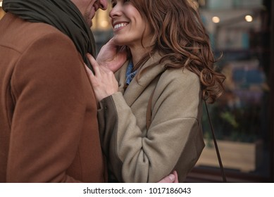 Close up of affectionate man touching female face with gentleness. Woman is looking at into his eyes and smiling. Lovers are standing and hugging on street