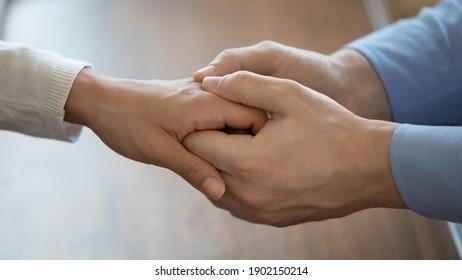 Close up affectionate man touching woman hand, comforting and supporting, expressing love and care, helping to overcome problems, encouraging and understanding, trusted relationship concept