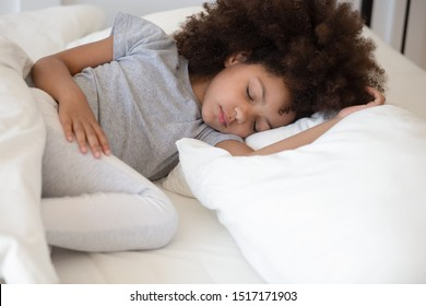 Close up african 6 years old adorable girl closed eyes lying in bed sleeping on white bed clothes comfortable mattress memory foam pillow, good night sweet dreams health care, real life moment concept