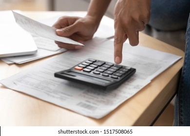 Close up african accountant woman hands holds paper cheque receipt count incomes doing paperwork, housewife check invoices calculates sales draft bills using calculator, managing family budget concept
