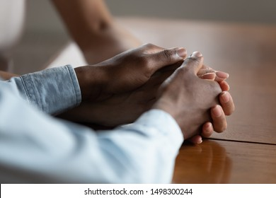 Close up of african American couple hold hands on wooden table make peace reconcile after fight, biracial husband and wife show love, care and support, have romantic intimate moment. Devotion concept