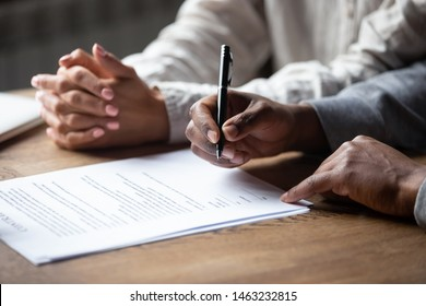 Close up of african American husband put signature on contract buying first house with wife, multiracial couple sign agreement closing deal with realtor or banker, taking property loan or mortgage