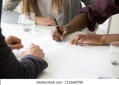 Close up of African American husband signing ownership contract buying first house with white wife, spouses closing deal with realtor or broker purchasing shared property or taking loan for apartment