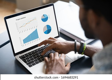 Close up of african American male worker busy working on modern laptop analyzing financial statistics, biracial man employee brainstorm preparing business project or startup plan on computer