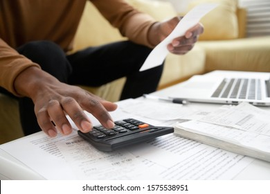 Close up of african American man calculating using machine managing household finances at home, focused biracial male make calculations on calculator paying bills, account taxes or expenses - Shutterstock ID 1575538951