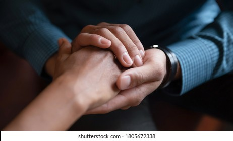 Close up African American man comforting woman, holding hands, expressing love and support, empathy, apologizing or saying sorry, family reconciliation, understanding in relationship