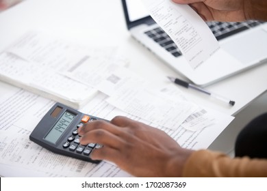Close up african american man hand using calculator and laptop for calculating finance. Businessman taxing, accounting, statistics and credit analytic for mortgage payment.