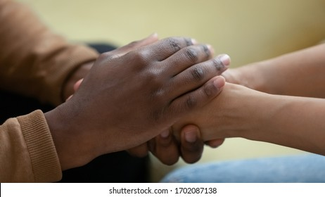 Close up african american man hands holding upset depressed woman, comforting wife for supporting frustrated disappointed girlfriend having life problem, showing love and support.