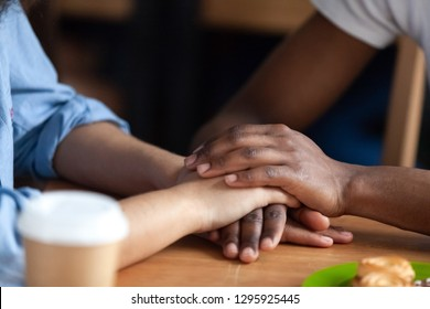 Close up African American man holding hand of mixed race girlfriend, young couple in love on date in coffeehouse, showing support or apologizing, saying sorry, trusted friends, true friendship