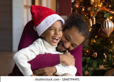Close up African American man hugging adorable son wearing festive red cap, family celebrating Christmas, sitting near decorated tree at home, loving dad and little child boy cuddling, winter holiday