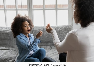 Close up African American mother teaching disabled daughter, showing symbols, little girl practicing sign language, repeating sounds, involved in speaking lesson with teacher at home, hearing loss
