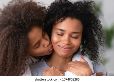 Close up African American teen daughter embracing smiling mother, kissing on cheek, enjoying moment together, teenage girl showing love and care, congratulating with mothers day or birthday