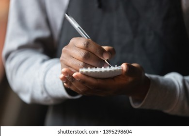 Close up African American waiter hands with notebook, taking customer order in cafe or restaurant, coffeehouse worker wearing black apron serving client, writing down, service concept