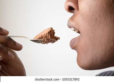 Close up African American woman mouth eating with homemade delicious Chocolate mousse or ice-cream spoon isolated on white background tasting coffee cafe lick, delicious taste Pleasure from eating