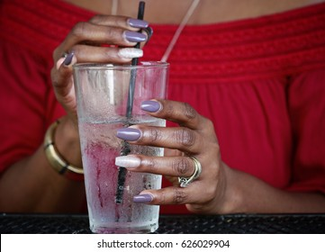 Close up of African American women's hands with beautiful manicure holding  glass with ice water