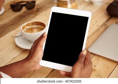 Close up of African American young female student sitting at a cafeteria, using modern electronic device, holding touchpad with blank screen for your advertisement. Technology and communication