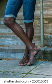 Close up of african black african american man legs, while wearing blue jean shorts and brown sandals