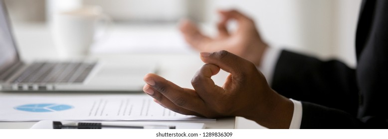 Close up african businessman sitting at desk near laptop stress relief at workplace, mental health internal balance concept, horizontal photo banner for website header design with copy space for text