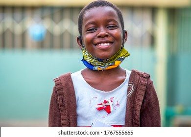 Close up of African child wearing homemade mask for protection,laughing and looking at camera-concept on children or student lifestyle in covid-19 pandemic