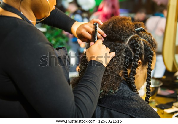 Close up african hairstylist braided hair of afro american female client in the barber salon. Black healthy hair culture and Style. Stylish therapy professional care concept. Selective focus