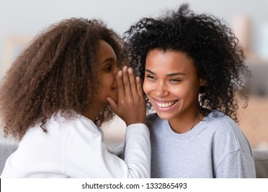Close up african mother best friend enjoy time gossiping with daughter, younger sister whispering secret in ear of confidant person, teenager girl chatting with nanny. Concept of trustworthy relations