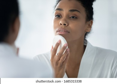 Close up African woman do evening routine cleanses skin using natural facial sponge, gently remove dirt, beauty tool helps renew revitalize skin, keep face perfect, massage procedure, skincare concept