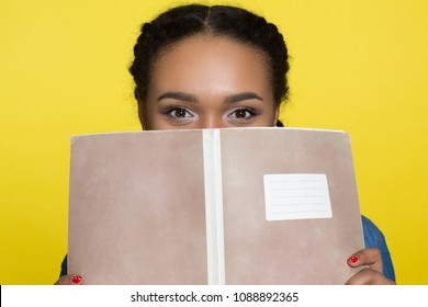 Close up of an African woman hiding half of her face behind a notebook posing on yellow background. Cheerful woman being playful and flirty covering her face with a book. Reading and intelligence