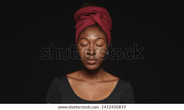 Close up of african woman isolated on black background with eyes closed. African female with a cloth wrapped on head with closed eyes.