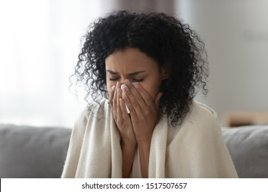 Close up african woman sit on couch covered with warm plaid holding handkerchief blowing runny nose to relief stuffy nose feels unhealthy having vitamin deficiency avitaminosis, seasonal flu concept