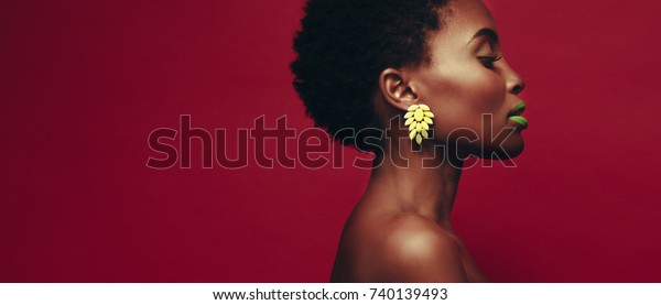 Close up of african woman wearing ear rings and vivid makeup against red background. Profile view of female model with beautiful skin.